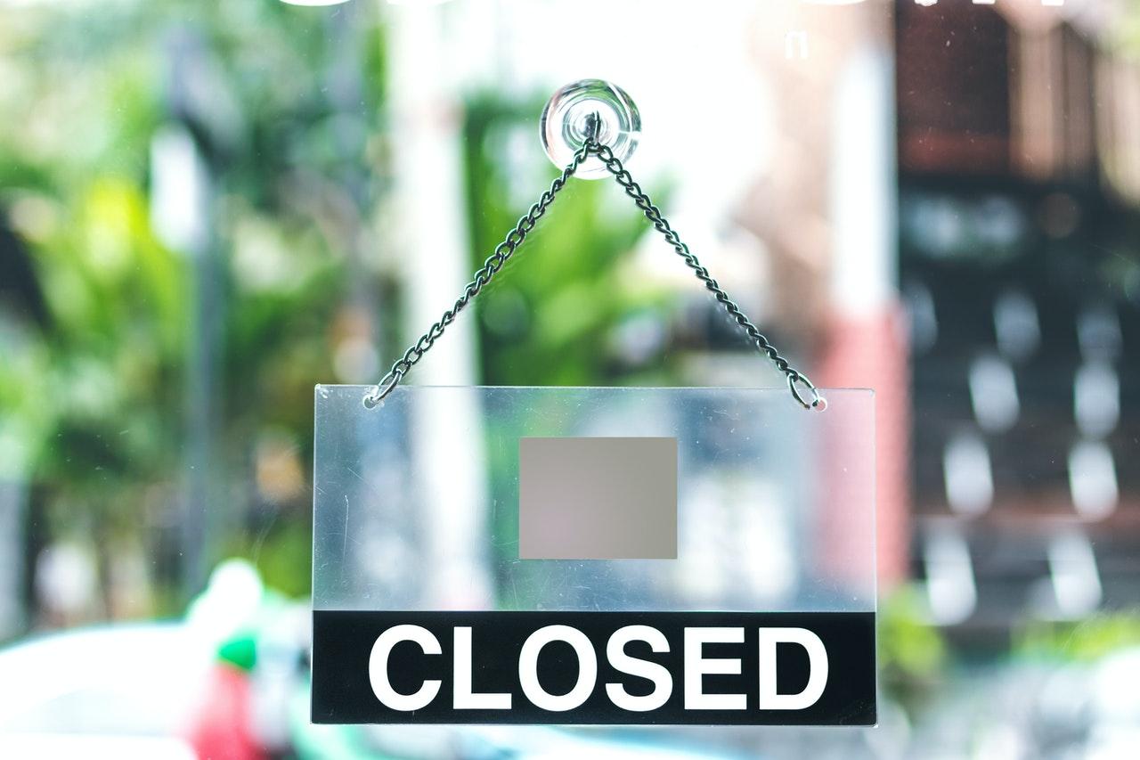 plexiglass-closed-sign-on-door-of-business