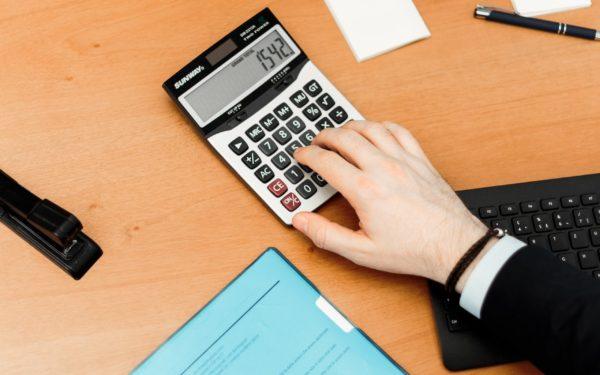 person-using-calculator-on-brown-desk