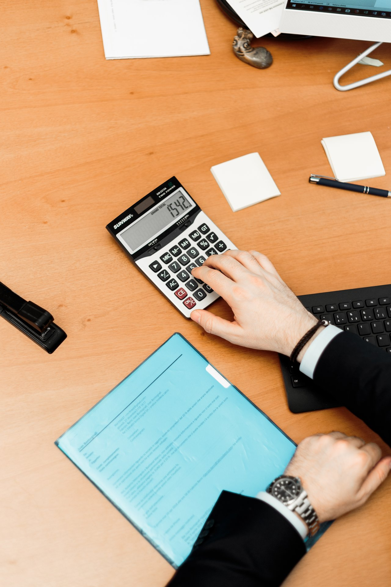 person-using-calculator-on-brown-desk