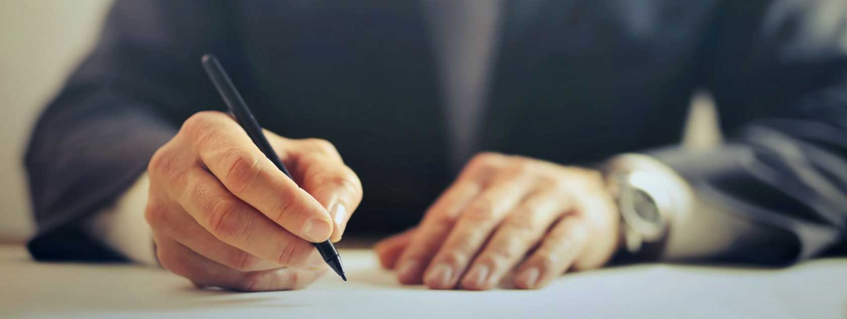 hands-of-a-man-writing-with-pen-sitting-at-desk
