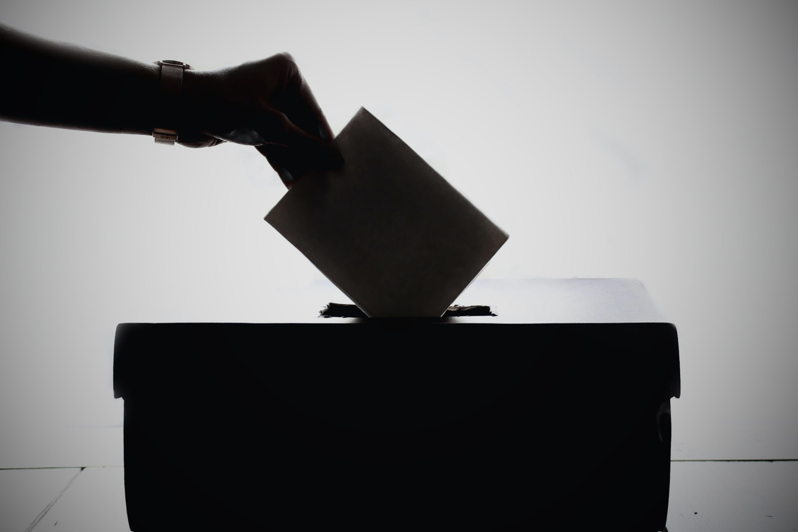 hand-putting-paper-in-ballot-box