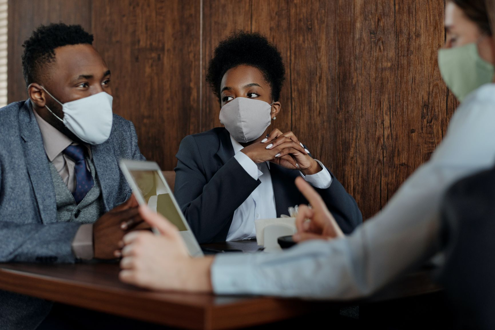 three-business-people-sitting-at-table-wearing-masks