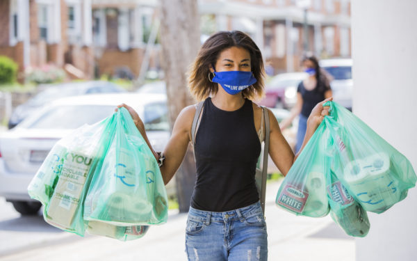 woman-walking-with-mask-while-carrying-groceries