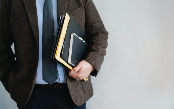man-holding-notebook-and-paperwork-under-his-arm