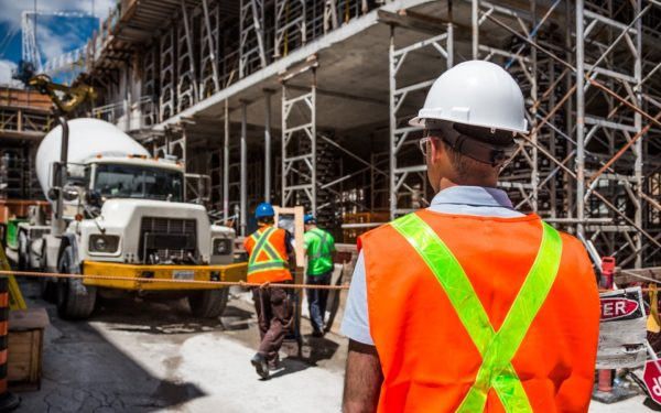 Man-in-hard-hat-with-back-turned-faces-construction-site