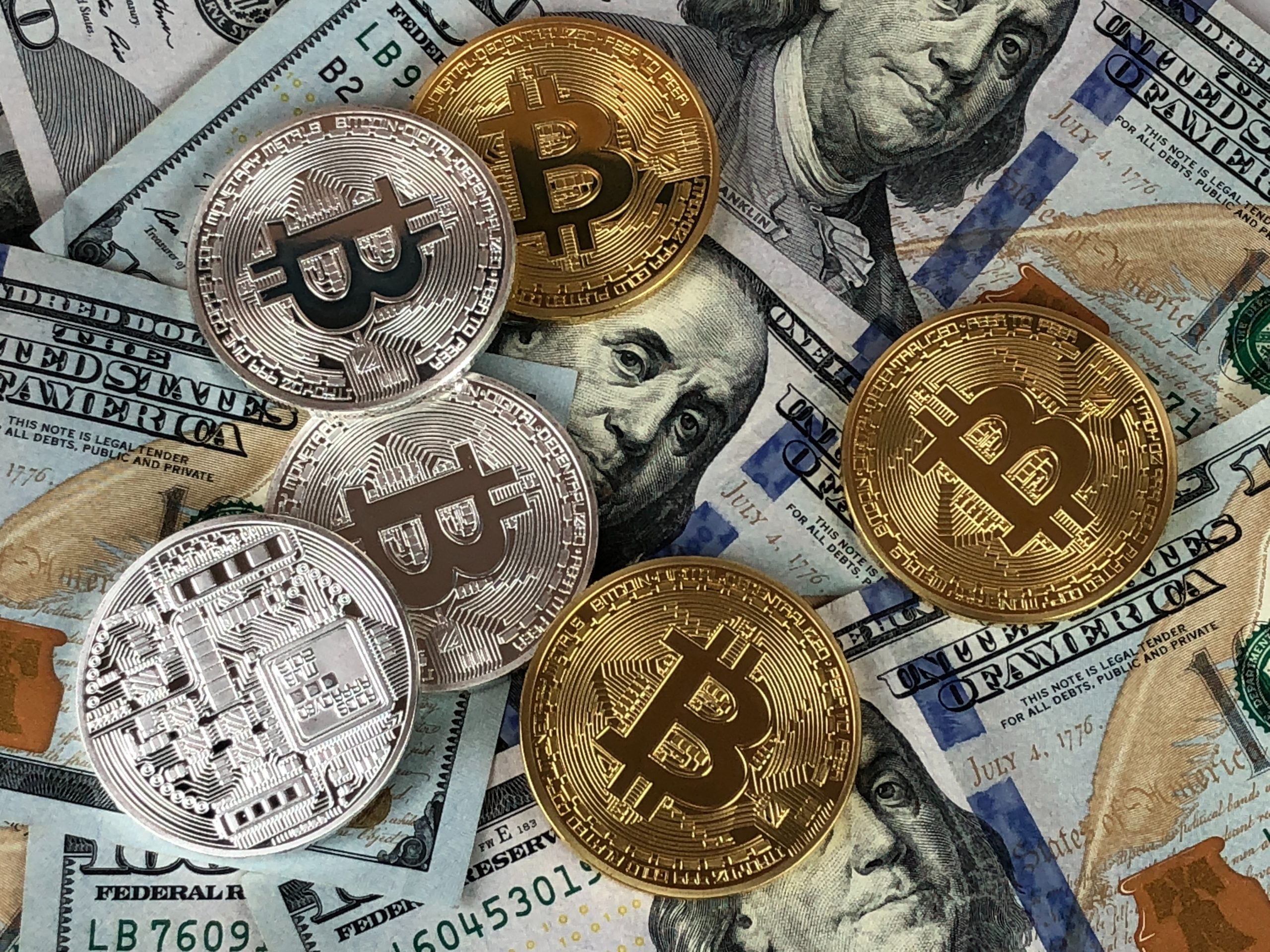 various-cryptocurrency-coins-laying-on-top-of-cash