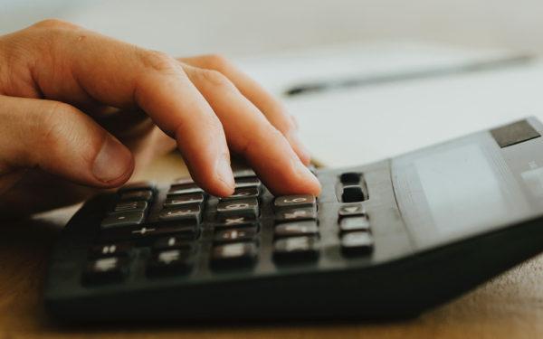 hand-typing-on-calculator-sitting-on-desk