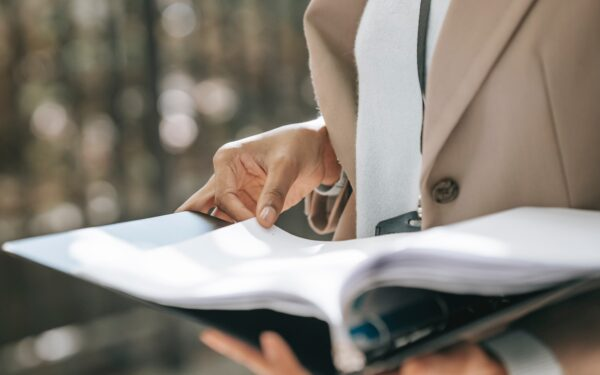 woman-in-beige-coat-holding-binder-of-papers