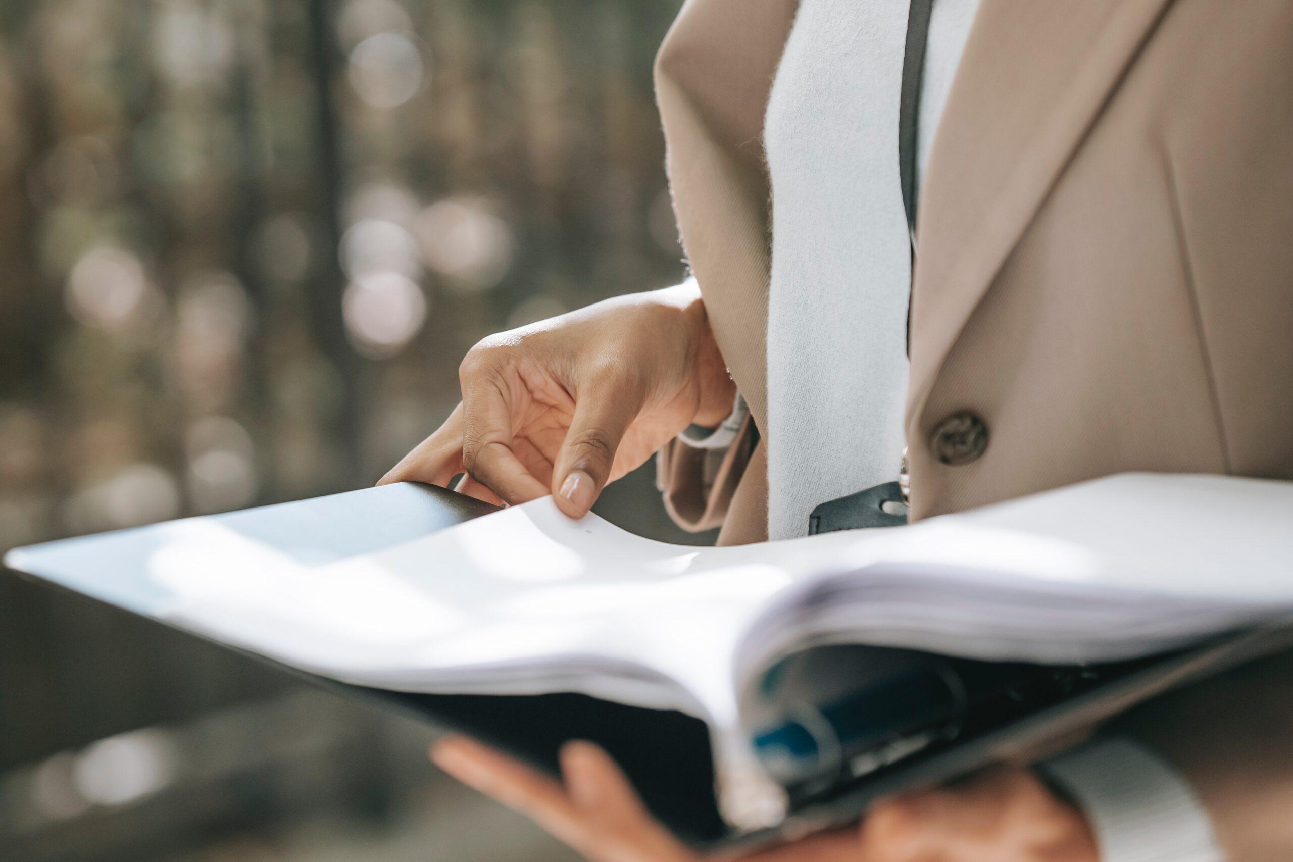 woman-in-beige-coat-holding-binder-of-papers