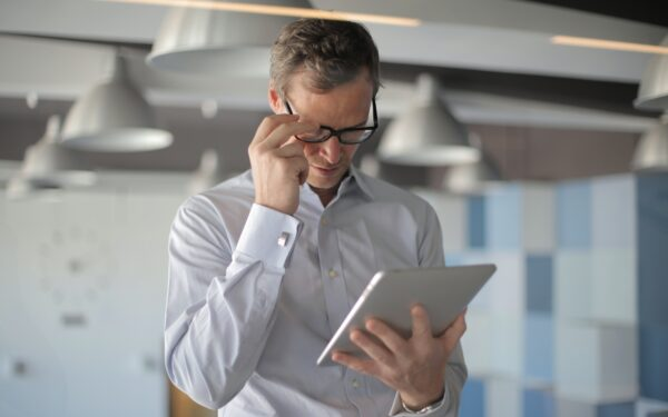 man-in-glasses-holding-ipad