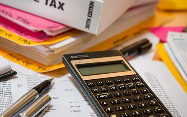 calculator-sitting-on-top-of-paperwork-next-to-income-tax-book