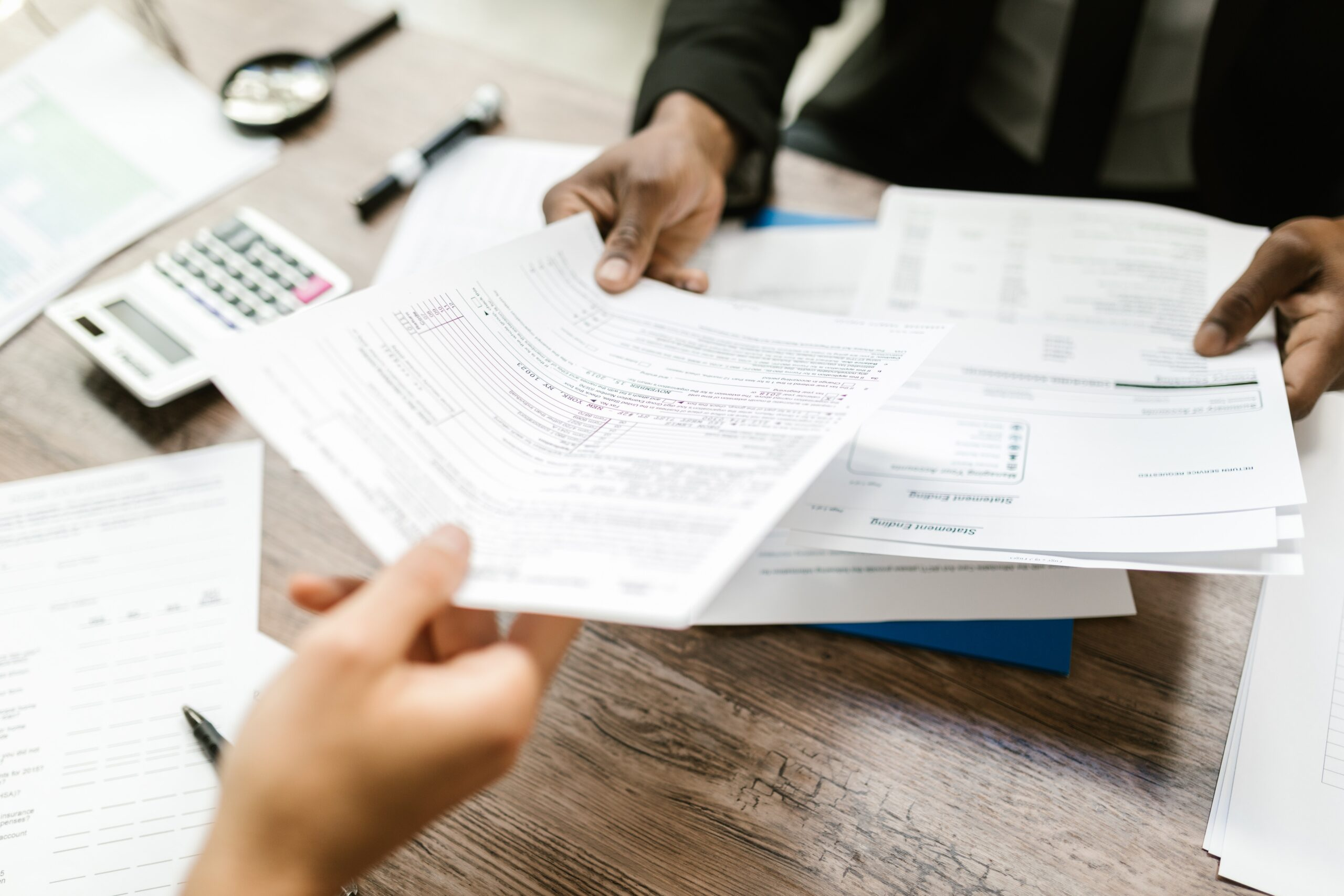 person handing another person paperwork