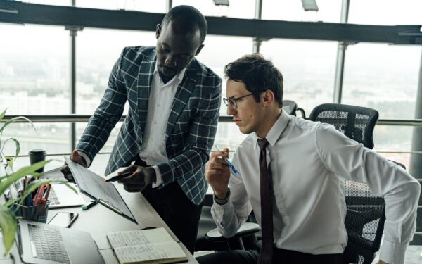 Two men in office discussing data