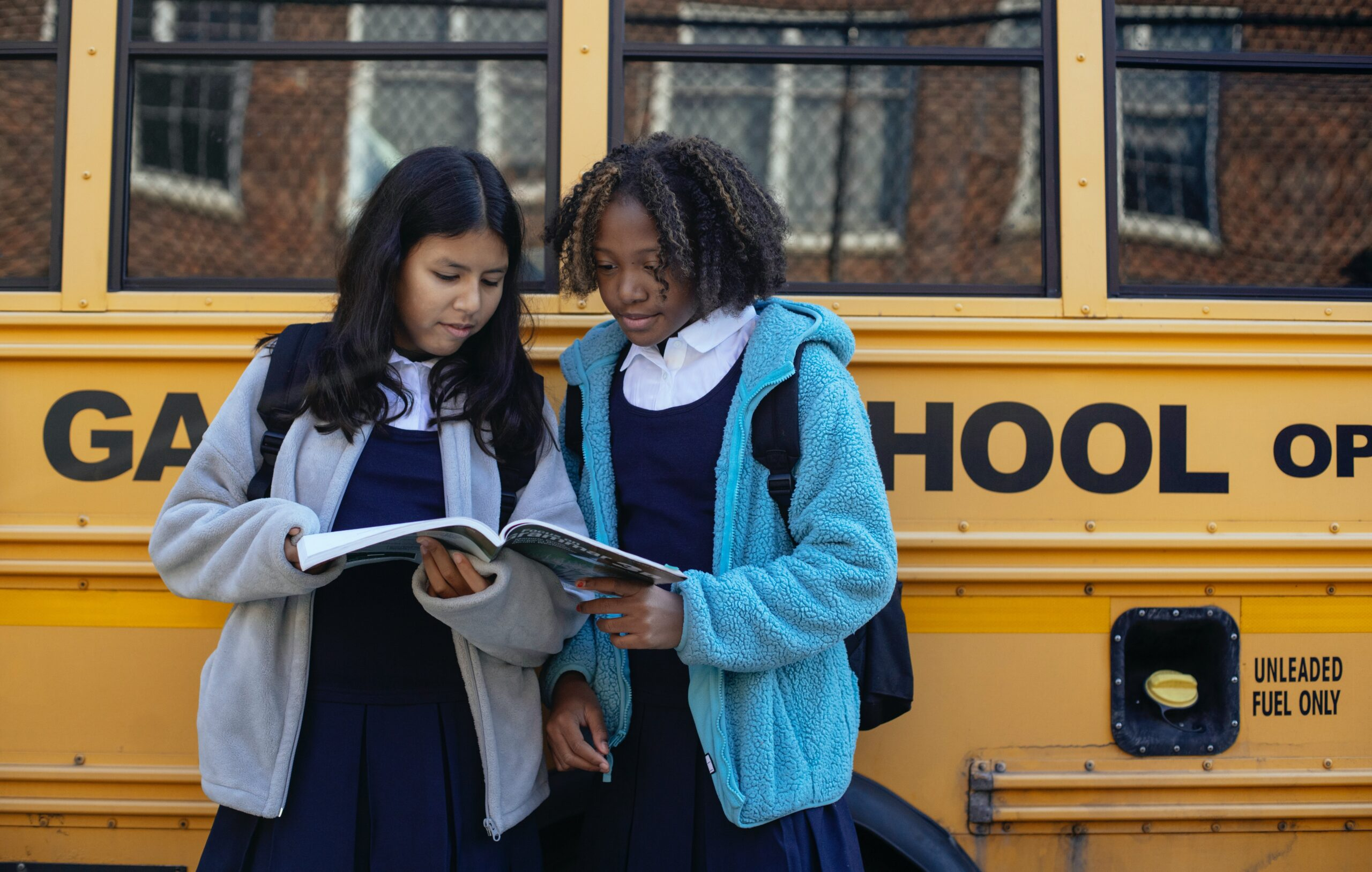 two girls dressed in school uniforms reading a textbook standing up